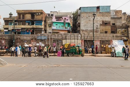 DELHI INDIA - 19TH MARCH 2016: People along streets in Delhi going about their daily life. Buildings and vehicles can be seen.