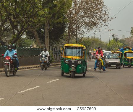 DELHI INDIA - 19TH MARCH 2016: A view along roads and streets in Delhi during the day. Lots of rickshaws people and other vehicles can be seen.