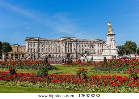 LONDON UK - 18TH JULY 2015: The outside of Buckingham Palace in London during the summer showing the Main Palace Victoria Memorial and flowers. People can be seen outside.
