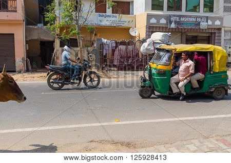 AGRA INDIA - 26TH MARCH 2016: Scenes along roads of Agra in India during the day. Tuk Tuk Rickshaws Motorbikes Cows buildings and people can be seen.