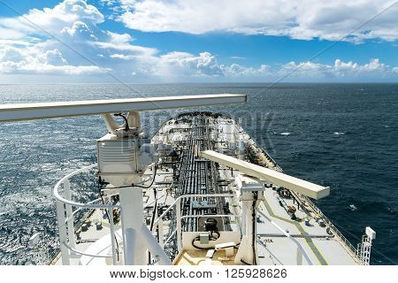 Crude oil tanker deck is proceeding through the ocean - view from radar mast