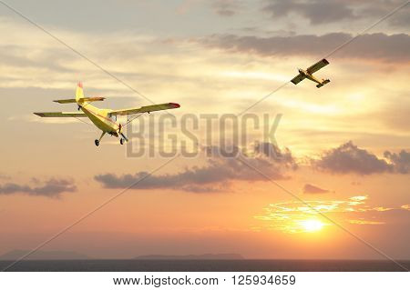 Two small yellow aircrafts seen against spectacular sunset over the sea