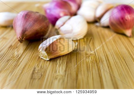 there are galics and shallots on the wood ** Note: Shallow depth of field