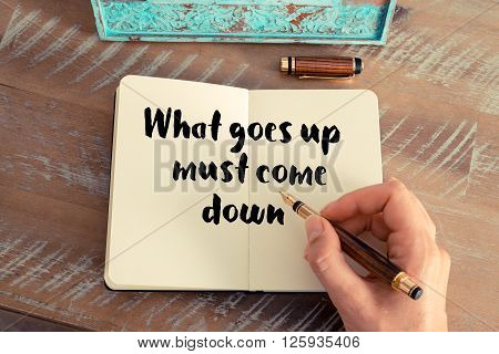 Handwritten quote What goes up must come down, as inspirational concept image