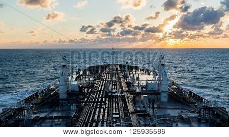 Sunset seascape with a oil tanker deck equipped with pipeline