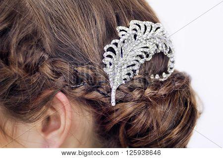 Close view of a fancy diamond brooch in brunette's hair.