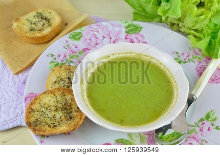 Bowl with fresh green pea soup (pottage) with pieces of garlic bread