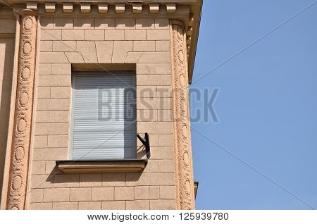 Window covered with sunblind on a renovated building facade and blue sky
