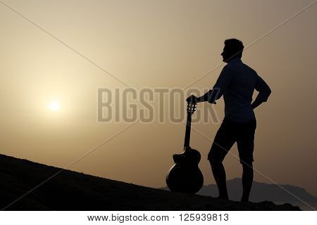dark silhouette of a young guitarist with his guitar at sunrise
