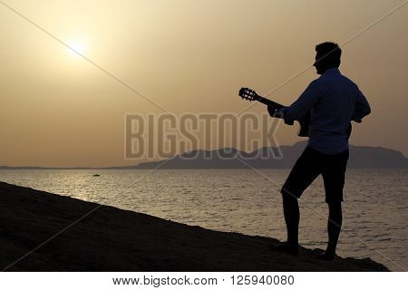 silhouette of a young man playing guitar at sunrise