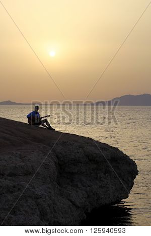 dark silhouette of a guitarist standing on the cliff overlooking the sea  and the sun rising