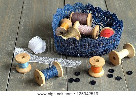 Knitted basket with coils colored sewing thread on gray wooden background.