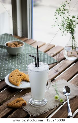 Glass with milkshake and cookie on wooden table in cafe. Selective focus.