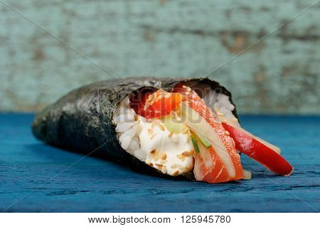 Temaki sushi with cream cheese fresh cucumber and bell pepper wrapped in nori copyspace
