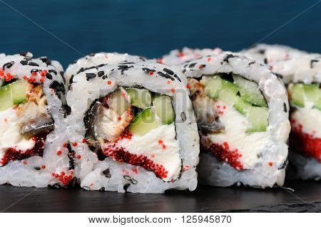 Set of square sushi rolls with vegs cream cheese and red roe on blue background closeup