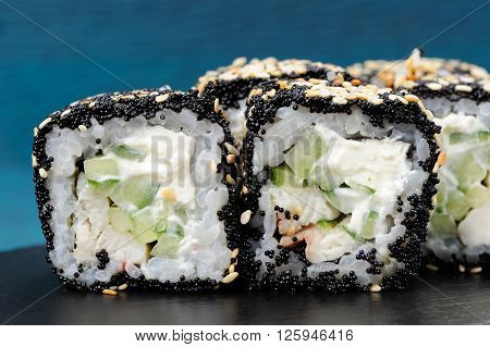 Japanese square rolls with black tobiko roe sesame seeds cream cheese and vegs closeup