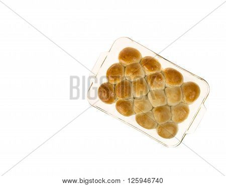 Pan of hot dinner rolls fresh from the oven in a glass pan isolated on white with copyspace.