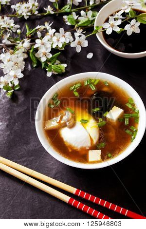 Japanese miso soup with egg, tofu, mushrooms and seaweed, daikon slices and soy sauce on the black stone with flowering branches
