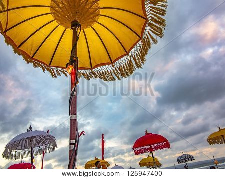 Traditional ceremonial umbrellas and flags on beach at ceremony Melasti before Balinese New Year and silence day Nyepi. Holidays festivals rituals art culture of Indonesian people and Bali island