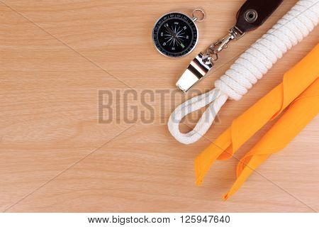 Orderliness White Scout Rope, Scarf, Whistle And Compass On Wooden Table.