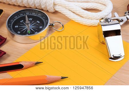 Orderliness White Scout Rope, Whistle, Compass, Pencil And Paper Note On Wooden Table.