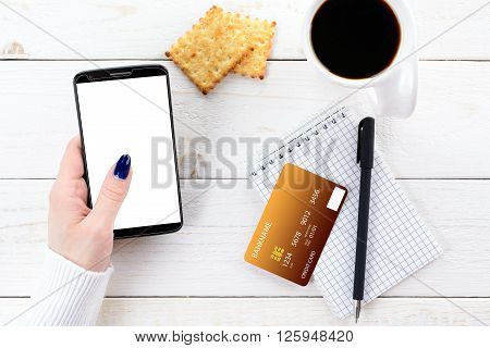 Woman Sitting At Table And Pays The Purchase Through Smartphone