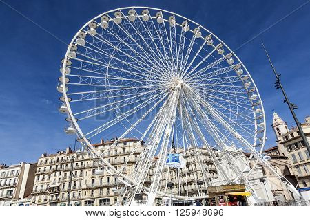 People Enjoy Big Ferris Wheel Against A Blue Sky In Marseilles