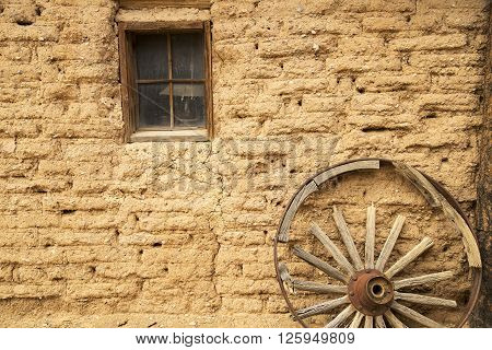 The adobe wall of old western cabin with a wagon wheel.