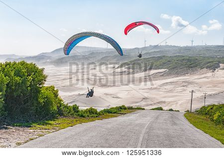 PORT ELIZABETH SOUTH AFRICA - FEBRUARY 27 2016: Silhouettes of two paragliders in the air against beach dunes at Beachview near Port Elizabeth
