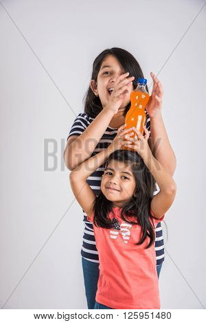 two indian girls with cold drink bottle, two asian girls posing with cold drink in pet bottle, 2 girl kid and cold drink, indian cute girls playing with mango juice or orange juice bottle