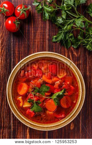 Goulash or stew in bowl served with parsley on wooden background top view.