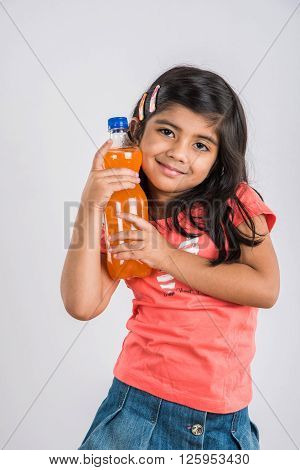 indian girl with cold drink bottle, asian girl drinking cold drink in pet bottle, girl kid and cold drink, indian cute girl with lemon or carbonated cold drink in plastic bottle, isolated on white