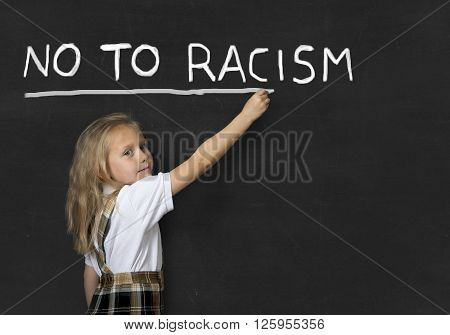 young sweet junior schoolgirl with blonde hair writing with chalk no to racism in classroom blackboard wearing school uniform in children education against racist behavior