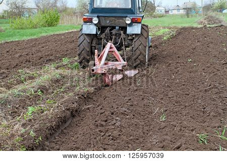 Tractor With Plow Fastened Spring Plowed Field. Spring Care Of The Farmer, The Opening Of The Season
