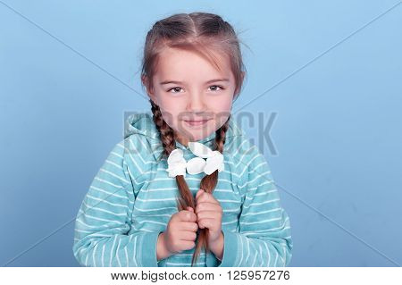 Smiling kid girl 3-4 year old posing over blue. Wearing blue striped hoodie. Holding two braids. Looking at camera.