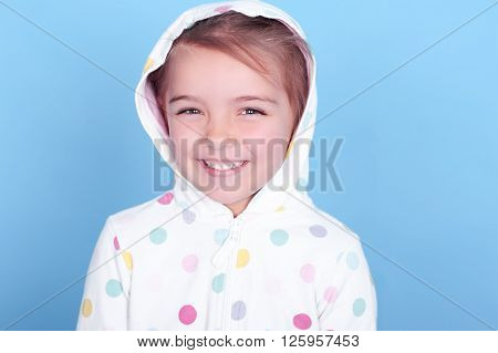 Laughing child girl 3-4 year old wearing hoodie with polka dots pattern over blue. Childhood. Positive emotions. Cheerful. Happiness.