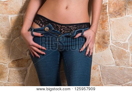 Sexy girl in blue jeans, undressing, part of the body, detail, close up