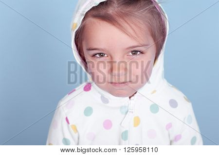 Angry kid girl wearing hoodie in room. Posing over blue. Close up portrait.