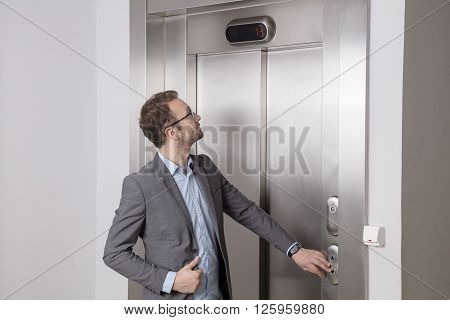 Young professional in suit waiting in front of the elevator