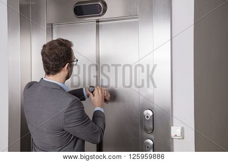 Businessman looking at his watch while waiting for the elevator