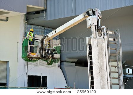 JOHOR, MALAYSIA -JANUARY 20, 2016: Construction workers standing in the mobile crane bucket while working at high level in the construction site in Malaysia.