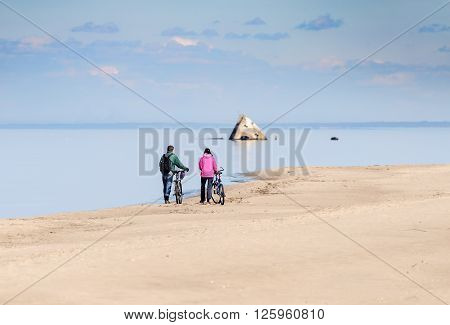 People with bicycles watching at sunken ship at Baltic sea coastline