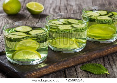 Very Fat Burning Detox Drink - Sassy Water: sliced cucumber lime ginger and mint in the three glasses on a wooden tray on an old wooden table close-up
