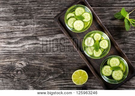 Very Fat Burning Detox Drink - Sassy Water: sliced cucumber lime and mint in the three glasses on a wooden tray on an old wooden tabletop view