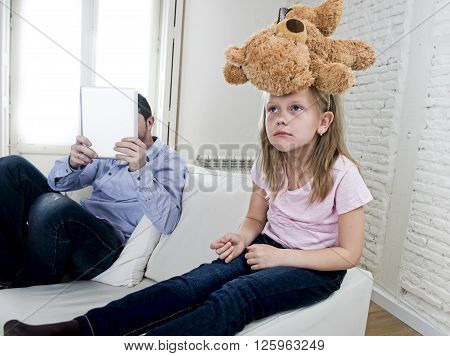 young internet addict father using digital tablet pad ignoring little sad daughter looking bored with teddy bear abandoned and disappointed with dad sitting on home couch sofa