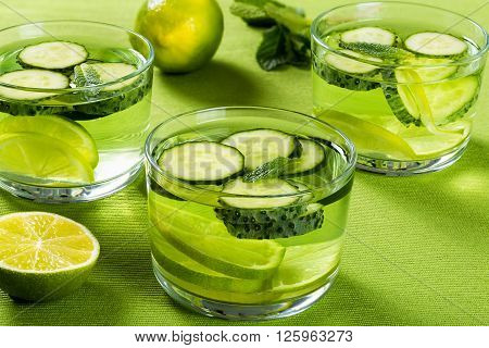 Very Fat Burning Detox Drink - Sassy Water: sliced cucumber lime and mint in the three glasses on a green table rib mat close-up