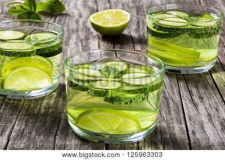 Very Fat Burning Detox Drink - Sassy Water: sliced cucumber lime and mint in the three glasses on a wooden tray on an old wooden table close-up