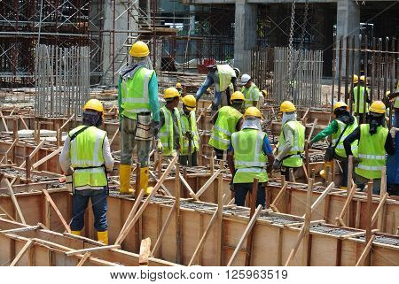 JOHOR, MALAYSIA -MARCH 10, 2016: Group of construction workers working at the construction site at Johor, Malaysia during daytime.