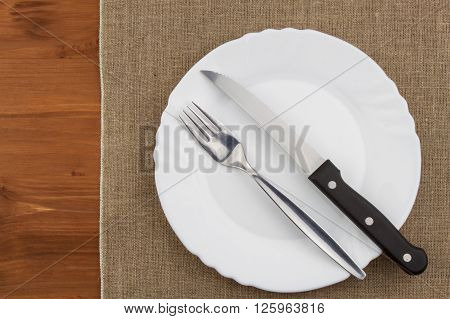 Empty white plate with knife and fork on a wooden table. Waiting for food. Home dining. Directly above view of table setting. Diet food.