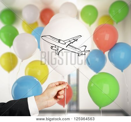 Male hand holding balloon with airplane print in room with many colorful balloons